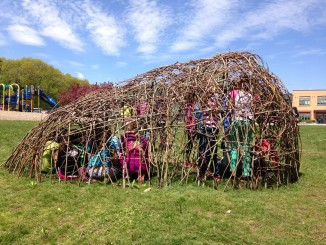 Students sit in the eco-art structure they built at their school in South Portland
